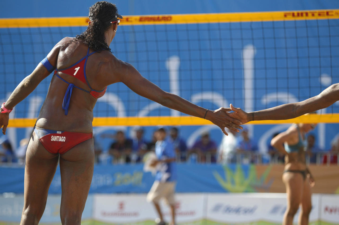 Puerto Rico's Yarleen Santiago, left, shake hands with teammate Yamileska Yatin during a women's beach volleyball match against Argentina at the Pan American Games in Puerto Vallarta, Mexico, Tuesday Oct. 18, 2011. (AP Photo/Ariana Cubillos)