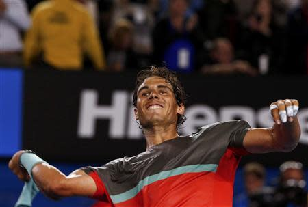 Nadal of Spain throws his sweatbands into the crowd as he celebrates defeating Federer of Switzerland in their men's singles semi-final match at the Australian Open 2014 tennis tournament in Melbourne