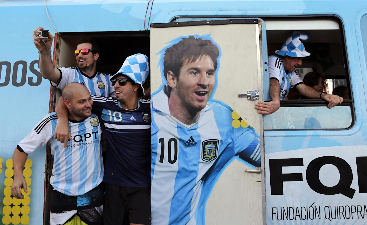 Argentine fans arrive in a bus decorated with a painting of soccer star Leonel Mesi at the Copacabana beach in Rio de Janeiro, Brazil, Saturday June 14, 2014. Waving flags and banners, more than a thousand Argentine fans, many dressed in their team's traditional blue and white, crowded the Copacabana beachfront ahead of Argentina's World Cup match against Bosnia-Herzegovina Sunday in Rio's iconic Maracana stadium.(AP Photo/Leo Correa)
