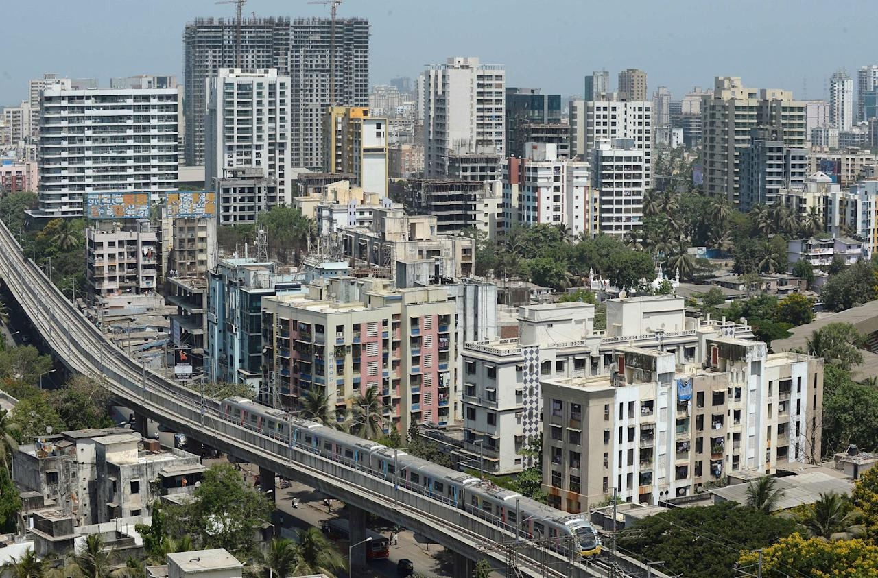 A Mumbai Metro train passes through a residential area during its first official safety trial run in Mumbai on May 1, 2013.  The Mumbai Metro transit system - whose full passenger service of the first phase will be thrown open to the public later this year, is designed to provide commuting relief to the city's residents who are caught in chronic congestion on the city's notoriously choked roads and is the country's third metro system following Kolkata and New Delhi.  AFP PHOTO/ INDRANIL MUKHERJEE        (Photo credit should read INDRANIL MUKHERJEE/AFP/Getty Images)