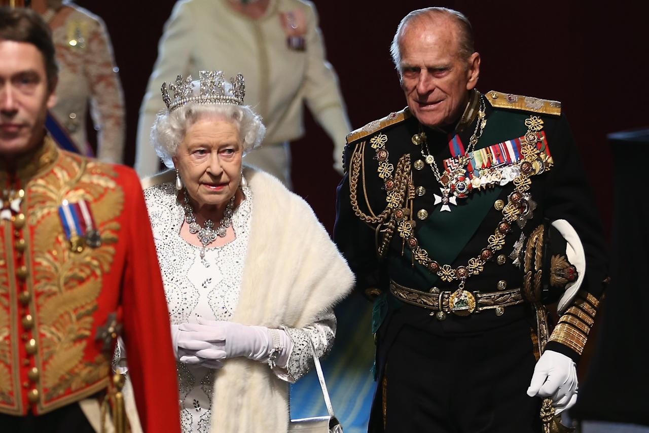 LONDON, ENGLAND - MAY 08:  Queen Elizabeth II, and Prince Phillip, Duke of Edinburgh are escorted through the Norman Porch of the Palace of Westminster after the State Opening of Parliament on May 8, 2013 in London, England. Queen Elizabeth II unveiled the coalition government's legislative programme in a speech delivered to Members of Parliament and Peers in The House of Lords. Proposed legislation is expected to be introduced on toughening immigration regulations, capping social care costs in England and setting a single state pension rate of 144 GBP per week.  (Photo by Dan Kitwood - WPA Pool/Getty Images)