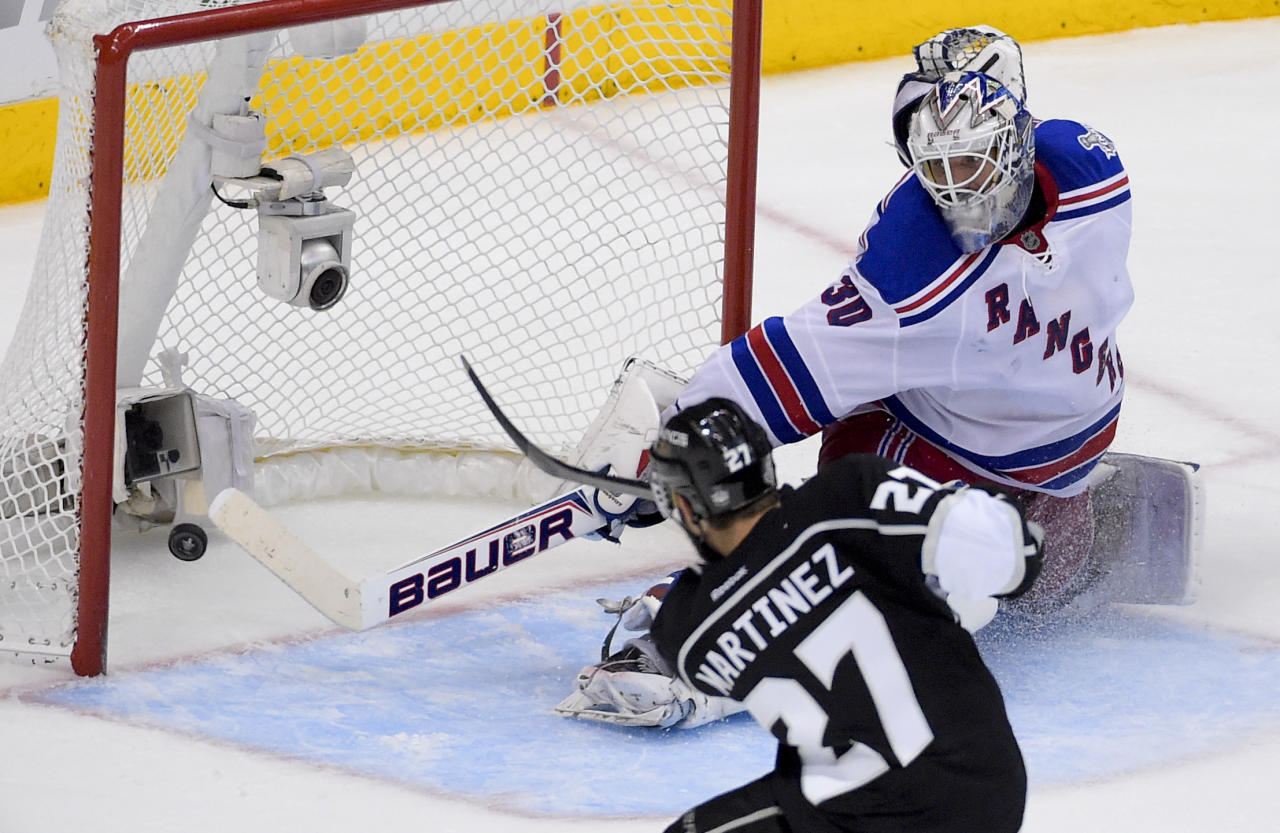 Los Angeles Kings defenseman Alec Martinez, left, scores the winning goal past New York Rangers goalie Henrik Lundqvist, of Sweden, during the second overtime period in Game 5 of an NHL hockey Stanley Cup finals, Friday, June 13, 2014, in Los Angeles.  (AP Photo/Mark J. Terrill)