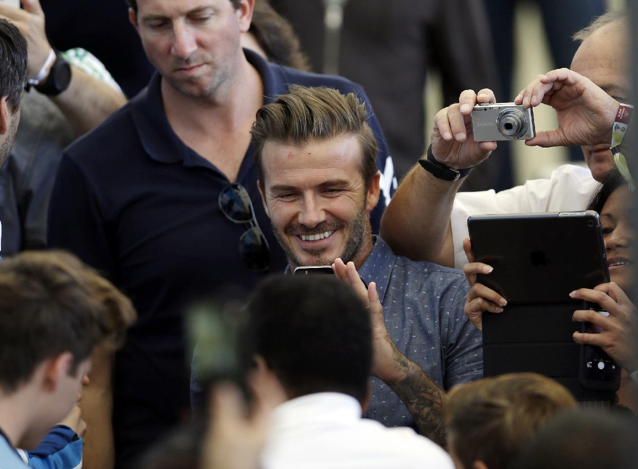 Former English soccer player David Beckham takes pictures as he arrives to attend  the World Cup final soccer match between Germany and Argentina at the Maracana Stadium in Rio de Janeiro, Brazil, Sunday, July 13, 2014. (AP Photo/Hassan Ammar)