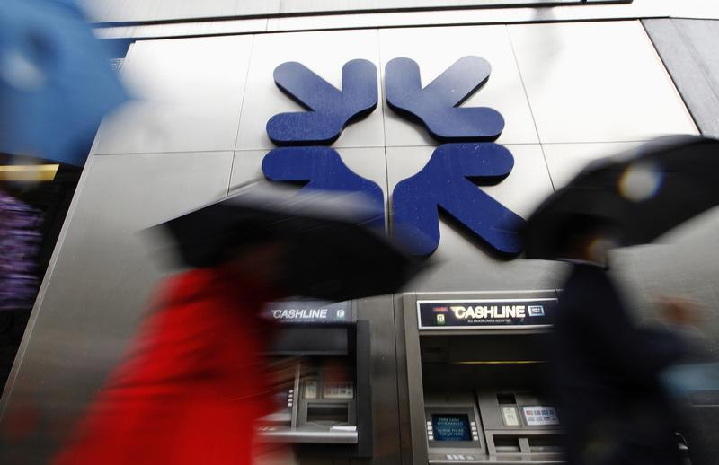 Morning commuters rush past a branch of RBS in London