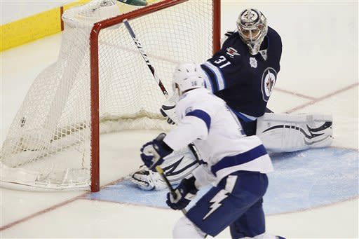 Tampa Bay Lightning's Teddy Purcell (16) scores on Winnipeg Jets goaltender Ondrej Pavelec (31) during second-period NHL hockey game action in Winnipeg, Manitoba, Saturday, April 7, 2012. (AP Photo/The Canadian Press, John Woods)