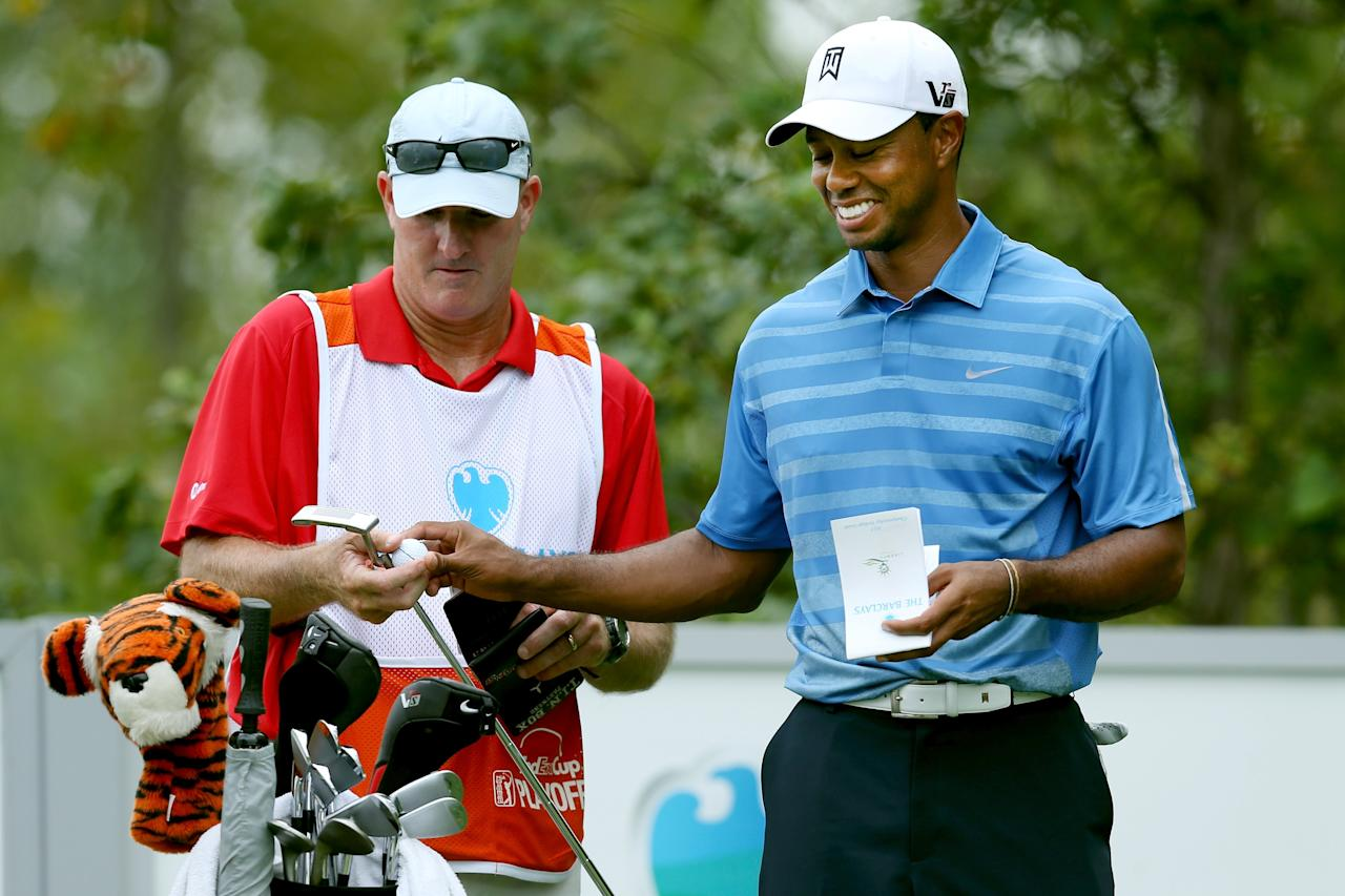 JERSEY CITY, NJ - AUGUST 22: Tiger Woods of the United States speaks with caddie Joe LaCava on the 16th tee during the first round of The Barclays at Liberty National Golf Club on August 22, 2013 in Jersey City, New Jersey. (Photo by Jeff Gross/Getty Images)