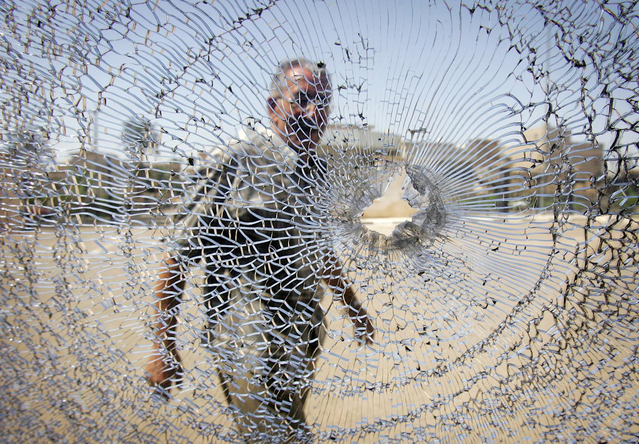 A man looks at the shattered windshield of a car after a bomb attack outside a Sunni mosque in Baghdad July 7, 2006. Bomb blasts rocked two Sunni mosques in Baghdad shortly after Friday noon prayers, killing at least five people and wounding nine, police said. REUTERS/Ceerwan Aziz