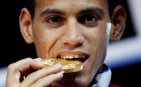 Gold medallist Robeisy Ramirez Carrazana of Cuba bites his medal during the presentation ceremony for the Men's Fly (52kg) boxing competition at the London Olympics August 12, 2012.     REUTERS/Murad Sezer (BRITAIN  - Tags: SPORT BOXING OLYMPICS)   - RTR36R6S