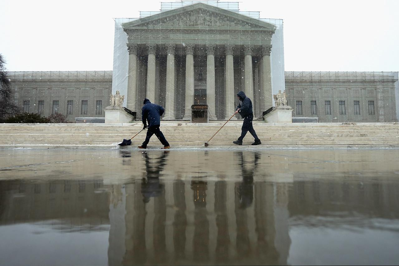 WASHINGTON, DC - MARCH 06:  Workers use shovels and brooms to remove a heavy mixture of snow and ice from the west front of the U.S. Supreme Court March 6, 2013 in Washington, DC. A late winter storm is expected to cover the Mid-Atlantic region after dropping almost a foot of snow across the the West and Midwest.  (Photo by Chip Somodevilla/Getty Images)
