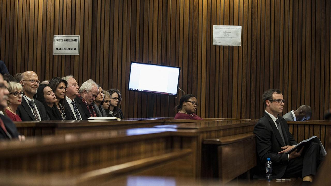 Oscar Pistorius, right, listens in court as state prosecutor Gerrie Nel sums up evidence in court at his murder trial in Pretoria, South Africa, Thursday, Aug. 7 2014. The chief prosecutor in Oscar Pistorius' murder trial said Thursday the double-amputee athlete's lawyers have floated more than one theory in a dishonest attempt to defend against a murder charge for his killing of girlfriend Reeva Steenkamp. (AP Photo/Mujahid Safodien, Pool)