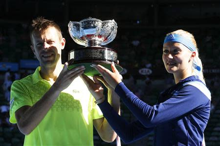 Mladenovic of France and Nestor of Canada pose with the trophy after winning their Mixed Doubles final match at the Australian Open 2014 tennis tournament in Melbourne