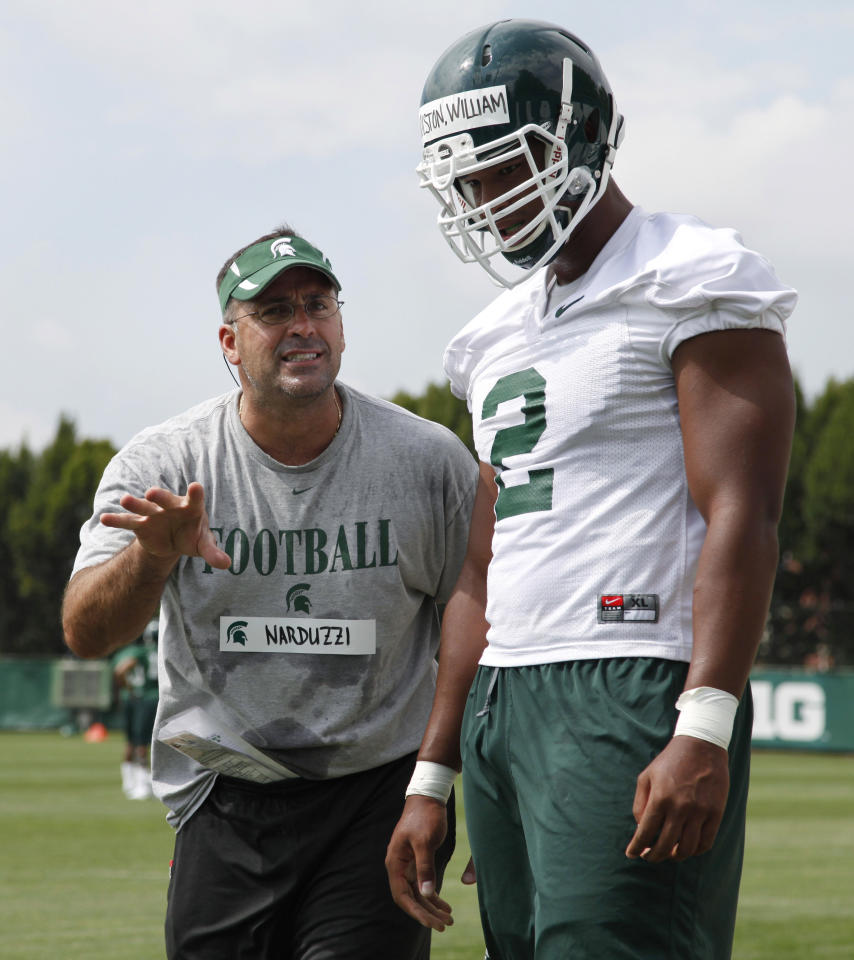 Michigan State defense coordinator Pat Narduzzi, left, gives instructions to defensive end William Gholston during the team's first NCAA college football practice of the season Sunday, Aug. 7, 2011, in East Lansing, Mich. (AP Photo/Al Goldis)