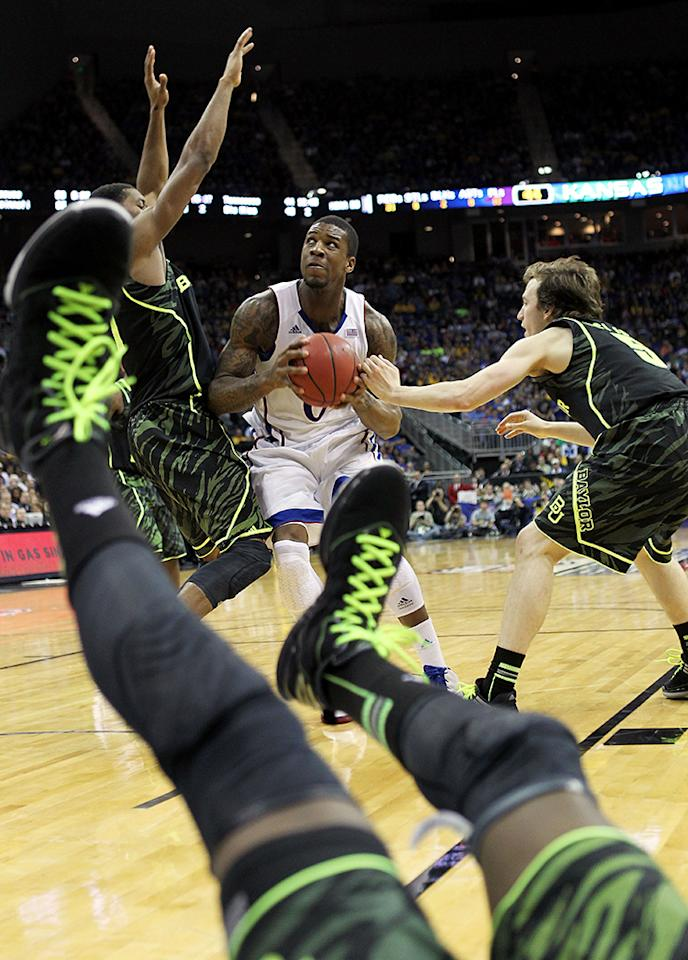 Quincy Miller #30 of the Baylor Bears falls backward out-of-bounds as Thomas Robinson #0 of the Kansas Jayhawks drives toward the basket during the NCAA Big 12 Semifinal game on March 9, 2012 at the Sprint Center in Kansas City, Missouri.  (Photo by Jamie Squire/Getty Images)
