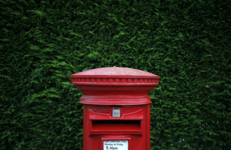 A Royal Mail post box stands on a street corner in Manchester