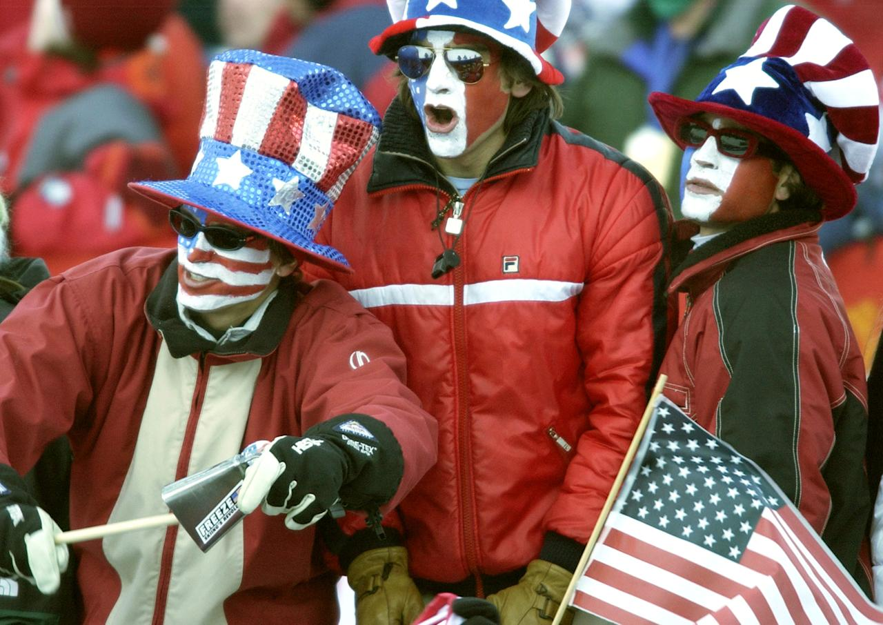 U.S. fans cheer as Jonny Moseley begins his qualification run during the men's freestyle competition at Deer Valley Resort in Park City, Utah on Tuesday, Feb. 12, 2002. Moseley finished fourth in the event. (AP Photo/Laura Rauch)