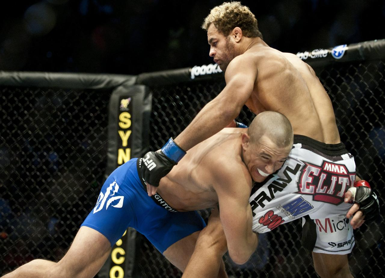 Georges St-Pierre (L) from Montreal, Canada pushing Josh Koscheck from Waynesburg OF US to the fence on the first round of the Ultimate Fighting Championship on December 11, 2010 at Bell Centre in Montreal, Quebec, Canada.    AFP PHOTO / ROGERIO BARBOSA  P PHOTO/ ROGERIO BARBOSA (Photo credit should read ROGERIO BARBOSA/AFP/Getty Images)