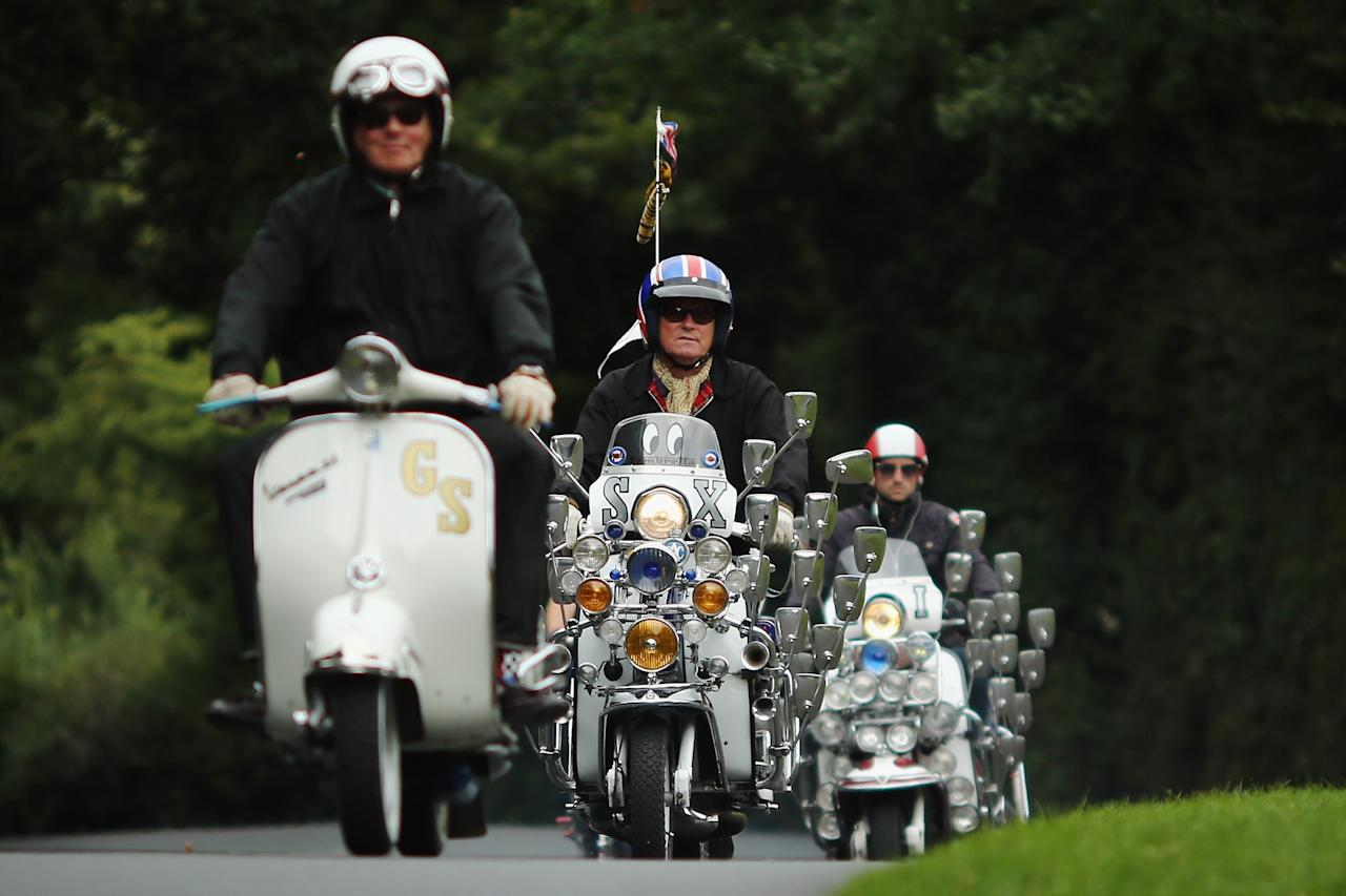 RYDE, ENGLAND - AUGUST 24: Scooter riders makes their way along a country lane during the the Isle of Wight International Scooter Rally on August 24, 2013 in Ryde, England. The annual event, which is organized by the British Scooter Rally Association and The VFM Scooter Collective, attracts around 6000 riders each year and has been running since 1980. The scooter in 1960's Britain was a fashion statement and the often heavily customized bikes, usually an Italian Vespa or Lambretta, became synonymous with the Mod scene. They provided an inexpensive mode of transport and escapism to an upwardly mobile youth at a time when public transportation stopped early. The Vespa was depicted on the cover of 'The Who's Quadrophenia album in 1973. (Photo by Dan Kitwood/Getty Images)