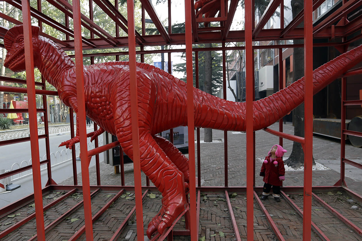 A child looks at a dinosaur sculpture designed by Chinese artist Sui Jianguo.