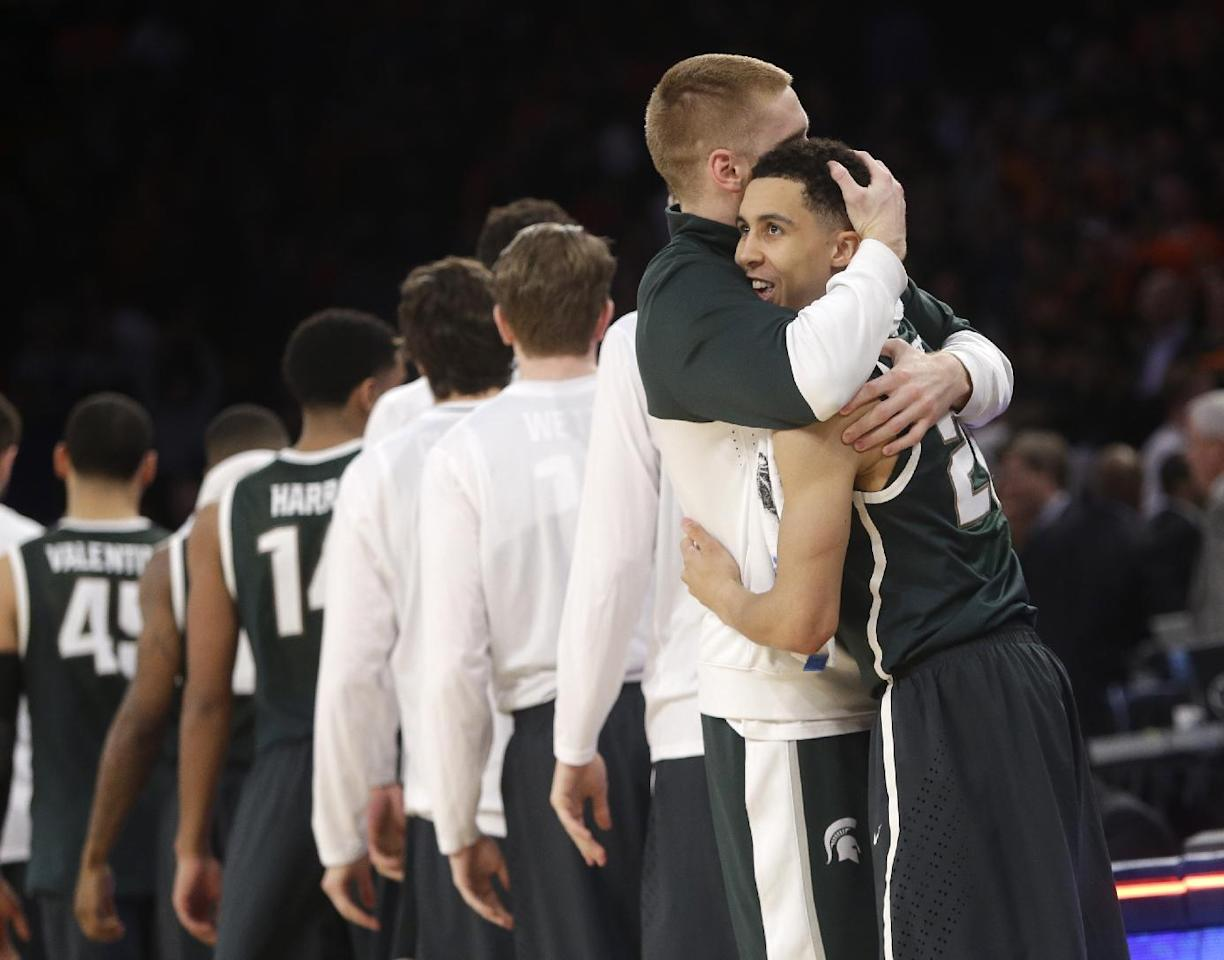 Michigan State's Russell Byrd, second from right, and Travis Trice embrace after their team defeated Virginia 61-59 in a regional semifinal of the NCAA men's college basketball tournament, Saturday, March 29, 2014, in New York. (AP Photo/Frank Franklin II)