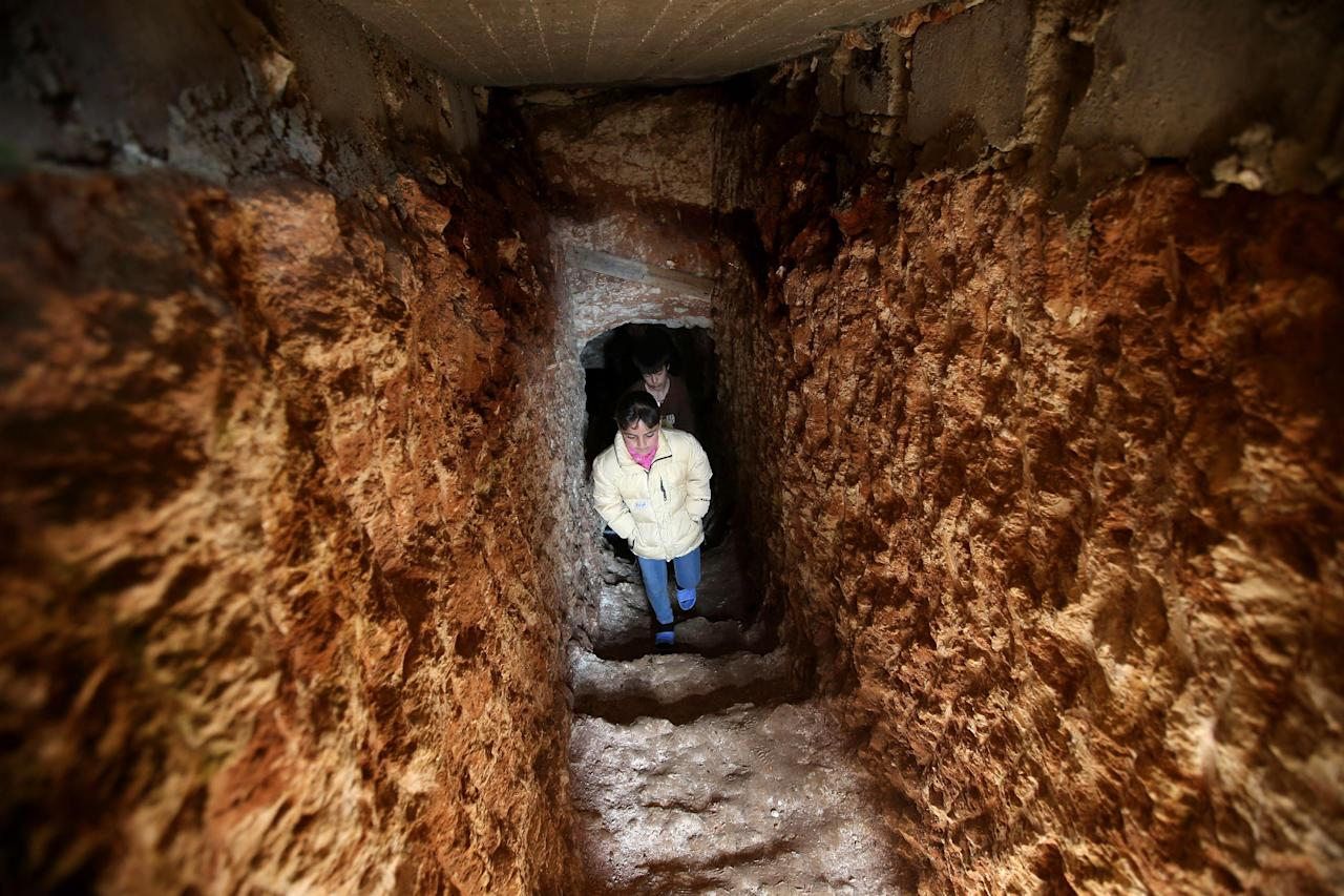 Syrian children, walk out of an underground tunnel that their father made with a jackhammer for shelter from Syrian government forces shelling and airstrikes, at Jirjanaz village, in Idlib province, Syria, Thursday, Feb. 28, 2013. Across northern Syria, rebels, soldiers, and civilians are making use of the country's wealth of ancient and medieval antiquities to protect themselves from Syria's two-year-old war. They are built of thick stone that has already withstood centuries, and are often located in strategic locations overlooking towns and roads. (AP Photo/Hussein Malla)