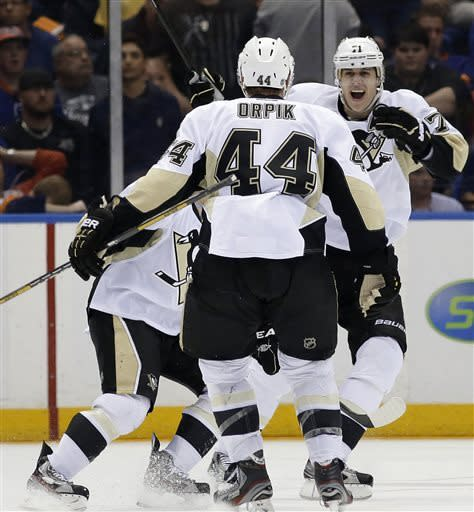 Pittsburgh Penguins center Evgeni Malkin, right, of Russia, congratulates defenseman Brooks Orpik (44), who scored the winning goal in overtime of Game 6 of a first-round NHL Stanley Cup playoff hockey series against the New York Islanders in Uniondale, N.Y., Saturday, May 11, 2013. The Penguins won 4-3. (AP Photo/Kathy Willens)