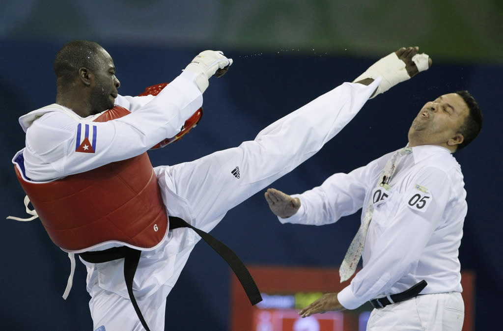 Cuba's Angel Valodia Matos, left, kicks match referee Sweden's Chakir Chelbat in the face during a bronze medal match against Kazakhstan's Arman Chilmanov in the men's taekwondo  80 kilogram class at the Beijing 2008 Olympics in Beijing, Saturday, Aug. 23, 2008. Matos attacked the official, throwing punches and kicks, after being declared the loser in his bronze medal match. (AP Photo/Matt Dunham)