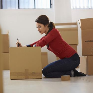 Woman-moving-to-new-apartment-with-boxes_web