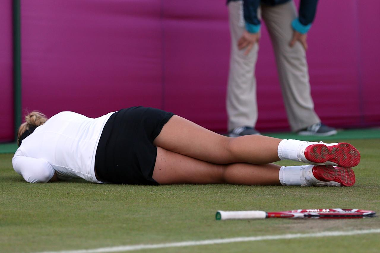 LONDON, ENGLAND - JULY 29:  Sabine Lisicki of Germany slips on the grass and falls to the floor during the Women's Singles Tennis match against Ons Jabeur of Tunisia on Day 2 of the London 2012 Olympic Games at the All England Lawn Tennis and Croquet Club in Wimbledon on July 29, 2012 in London, England.  (Photo by Clive Brunskill/Getty Images)