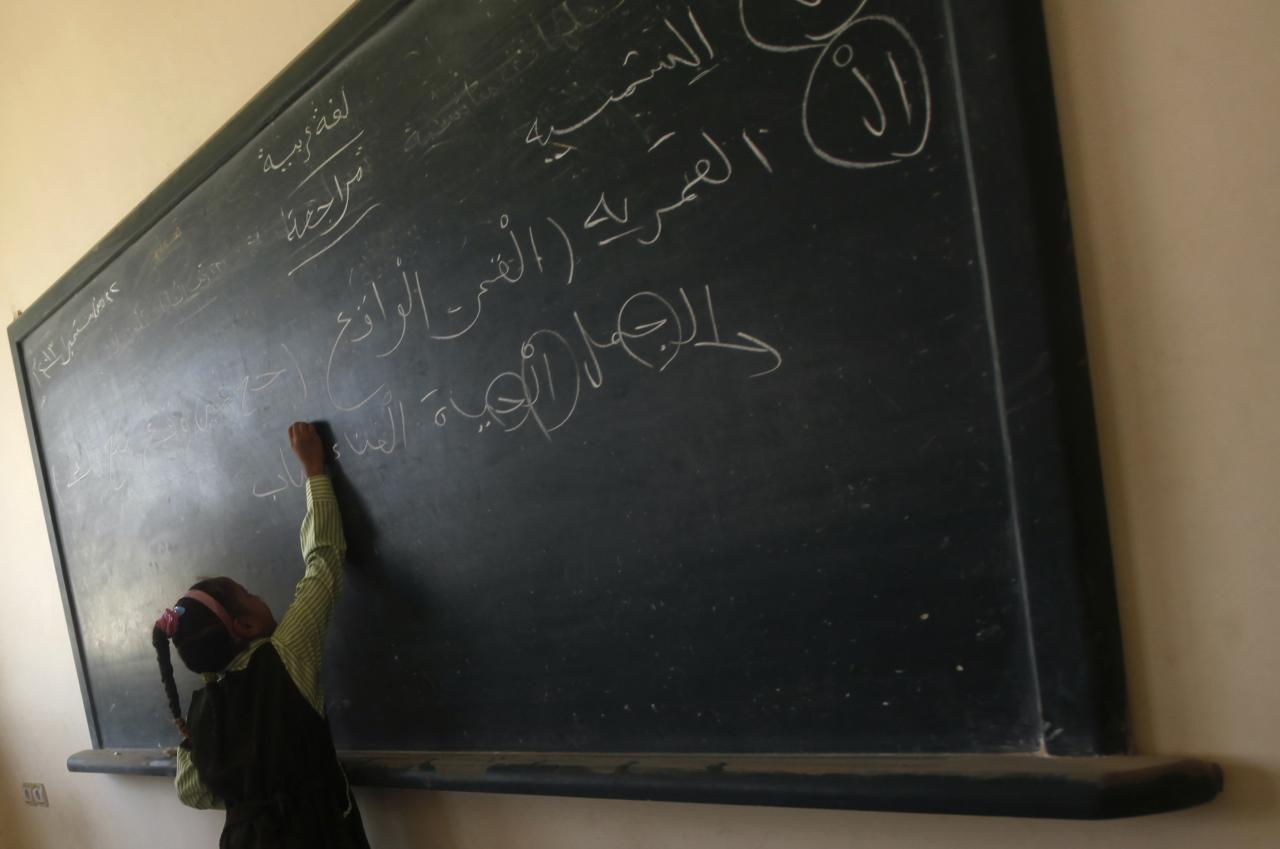 A girl writes on the blackboard on the first day of her new school year at a government school in Giza, south of Cairo September 22, 2013. Students resumed their studies at the beginning of the new academic year this weekend amid parental concerns of a possible lack of security after the summer vacation ends. REUTERS/Mohamed Abd El Ghany (EGYPT - Tags: POLITICS EDUCATION)
