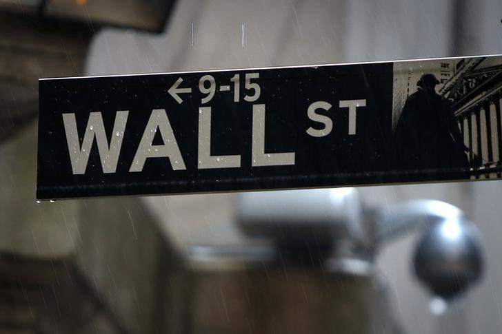 A Wall Street sign is pictured in the rain outside the New York Stock Exchange