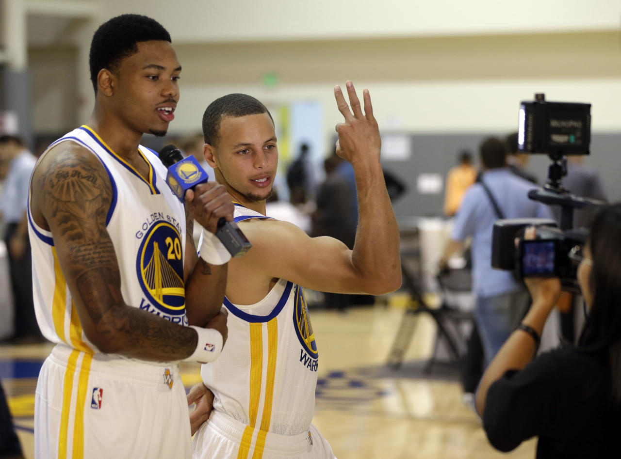 Golden State Warriors' Stephen Curry, right, jokes with teammate Kent Bazemore during NBA basketball media day on Friday, Sept. 27, 2013, in Oakland, Calif. (AP Photo/Marcio Jose Sanchez)