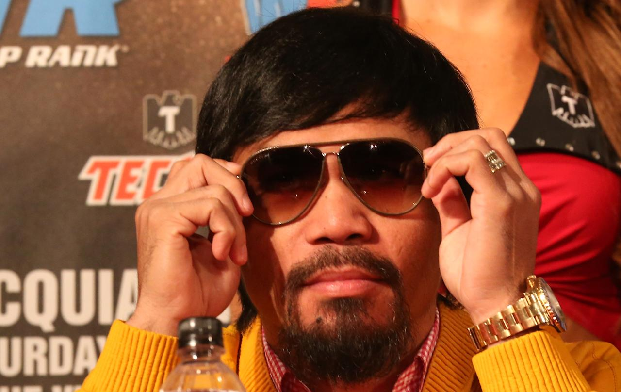 BEVERLY HILLS, CA - AUGUST 08: Manny Pacquiao puts on his sunglasses at a press conference previewing the upcoming match against Brandon Rios at Beverly Hills Hotel on August 8, 2013 in Beverly Hills, California. (Photo by Stephen Dunn/Getty Images)