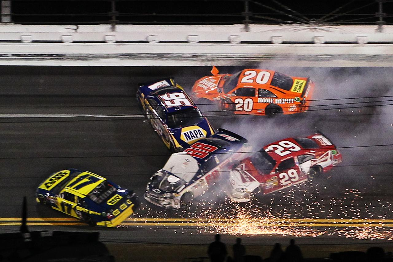 DAYTONA BEACH, FL - FEBRUARY 18:  Martin Truex Jr., driver of the #56 NAPA Auto Parts Toyota, Joey Logano, driver of the #20 The Home Depot Toyota, Dale Earnhardt Jr., driver of the #88 Diet Mountain Dew/National Guard Chevrolet, Matt Kenseth, driver of the #17 Best Buy Ford, and Kevin Harvick, driver of the #29 Budweiser Chevrolet, are involved in an crash during the NASCAR Budweiser Shootout at Daytona International Speedway on February 18, 2012 in Daytona Beach, Florida.  (Photo by Jamie Squire/Getty Images)