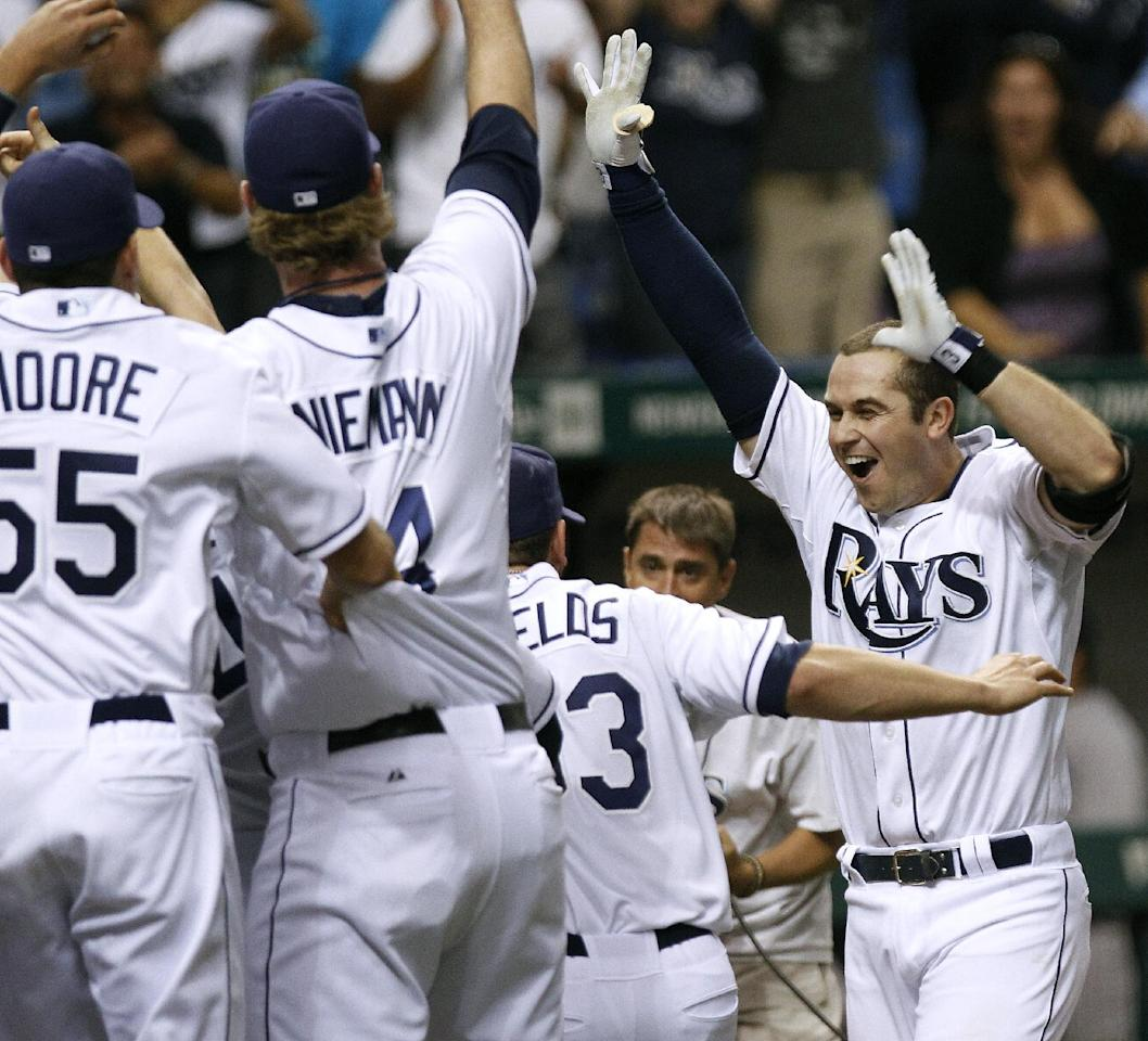 Tampa Bay Rays' Evan Longoria, right, celebrates with teammates after his home run in the 12th inning against the New York Yankees during a baseball game early Thursday, Sept. 29, 2011, in St. Petersburg, Fla. The Rays defeated the Yankees 8-7 and won the AL wild card. (AP Photo/Chris O'Meara)