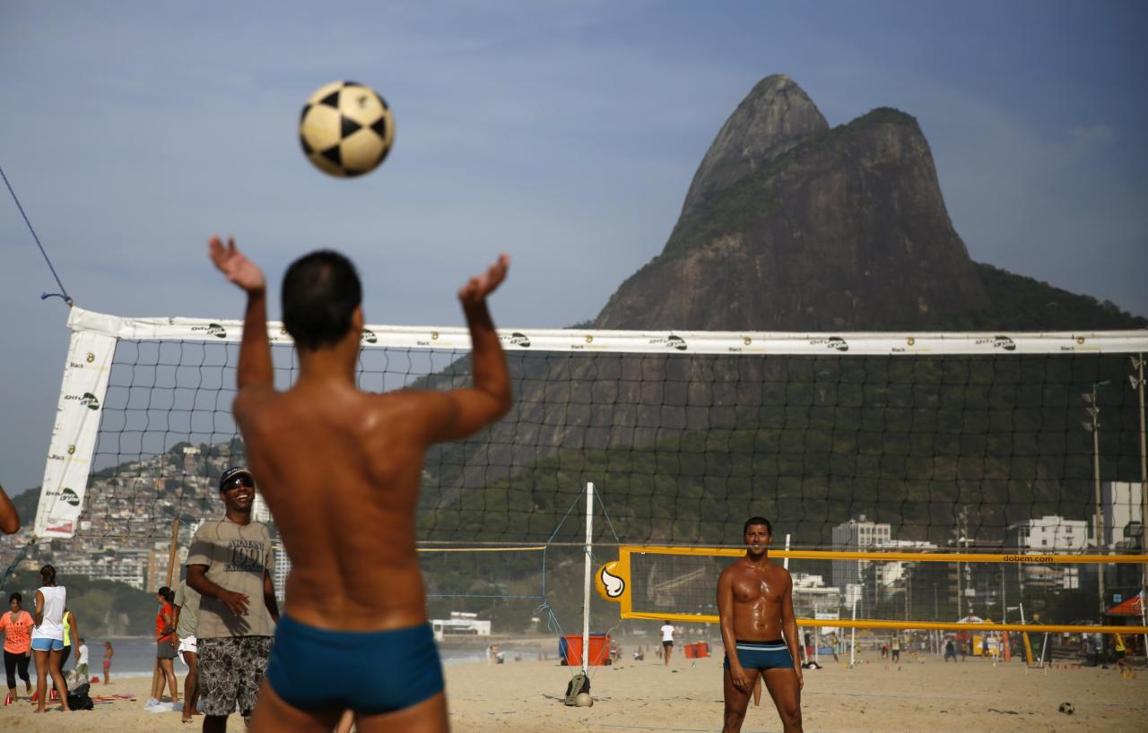 Residents play footvolley, a sport that combines both soccer and volleyball, on Ipanema beach in Rio de Janeiro April 9, 2014. REUTERS/Pilar Olivares (BRAZIL - Tags: SPORT SOCCER VOLLEYBALL SOCIETY)