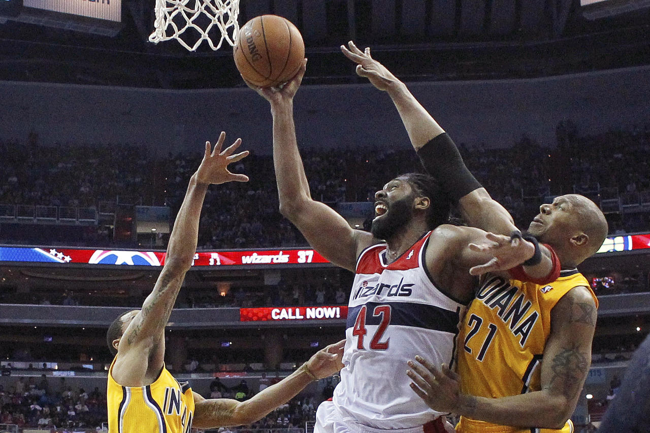 Washington Wizards forward Nene (42) of Brazil shoots between Indiana Pacers guard George Hill and Indiana Pacers forward David West (21) during the second half of Game 3 of an Eastern Conference semifinal NBA basketball playoff game in Washington, Friday, May 9, 2014. The Pacers won 85-63. (AP Photo/Alex Brandon)