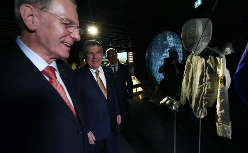 IOC President Bach poses next to his predecessor Rogge in front of Bach's fencing outfit for the Montreal 1976 Olympics at the Olympic Museum in Lausanne