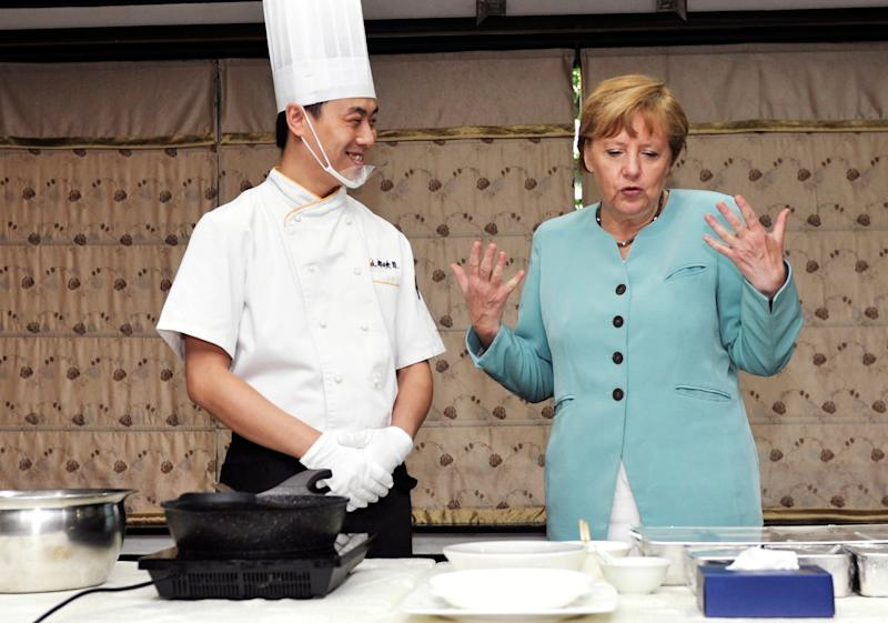 Angela Merkel learns how to make kung pao chicken from a cook at a restaurant in Chengdu, southwest China's Sichuan province on July 6, 2014