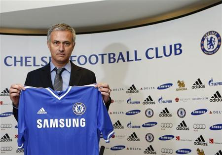 Newly reappointed Chelsea manager Jose Mourinho poses for photographers during a news conference at Stamford Bridge stadium in London