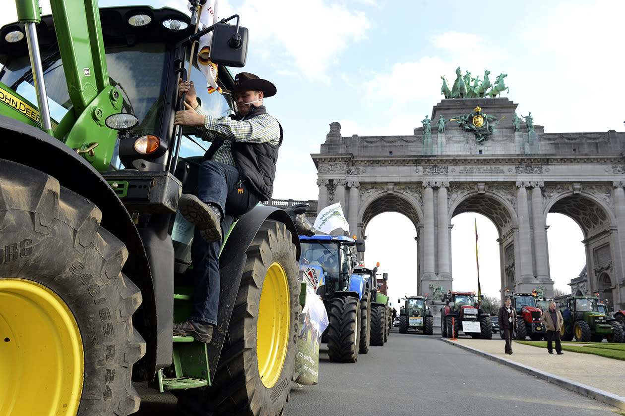A farmer climbs into his tractor as he joins European milk farmers in a drive into the European quarter in Brussels.