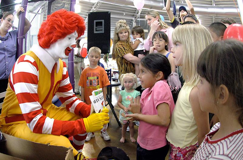 FILE - In this file photo taken May 18, 2006, Ronald McDonald visits with children at a McDonald's Restaurant in Roswell, N.M. Some branding experts think the McDonald's Corp. clowns' floppy red shoes and flaming-red hair are too hackneyed for iPod-savvy kids.  (AP Photo/Roswell Daily Record, Andrew Poertner, file)