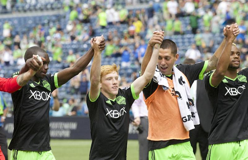 Along with Seattle Sounders teammates Jalil Anibaba, far left, Clint Dempsey, second from right, and Tristan Bowen far right, Xander Bailey acknowledges fans following a friendly soccer match against Tottenham Hotspur in Seattle, Saturday, July 19, 2014. The match ended in a 3-3 draw