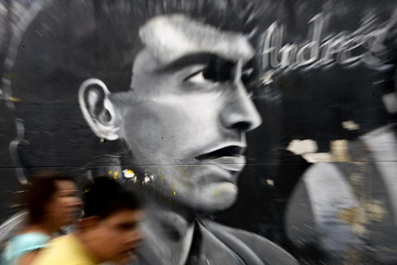 People walk by a mural painting depicting the late Colombian footballer Andres Escobar at the street in Medellin, Antioquia department, Colombia on July 1, 2014