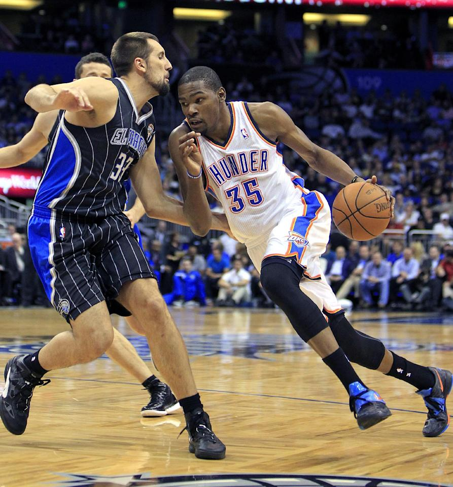 Oklahoma City Thunder's Kevin Durant (35) drives around Orlando Magic's Ryan Anderson (33) during the first half of an NBA basketball game Thursday, March 1, 2012, in Orlando, Fla. (AP Photo/John Raoux)