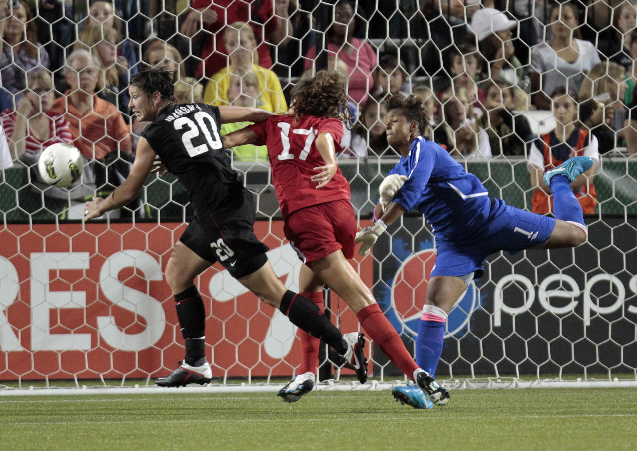 U.S. forward Abby Wambach, left, chases the ball after Canada goalkeeper Karina LeBlanc, right, knocked it out of the goal mouth during the first half of an international friendly soccer match in Portland, Ore., Thursday, Sept. 22, 2011. Defending in the middle is Canada's Lexi Marton. (AP Photo/Don Ryan)