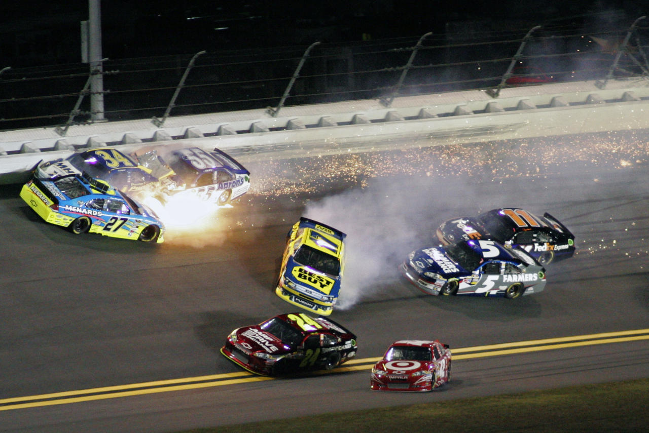 Paul Menard (27), David Ragan (34), Michael Waltrip (55) and Matt Kenseth (17) wreck coming out of Turn 1 during the NASCAR Budweiser Shootout auto race at Daytona International Speedway, Saturday, Feb. 18, 2012, in Daytona Beach, Fla. (AP Photo/Jim Topper)