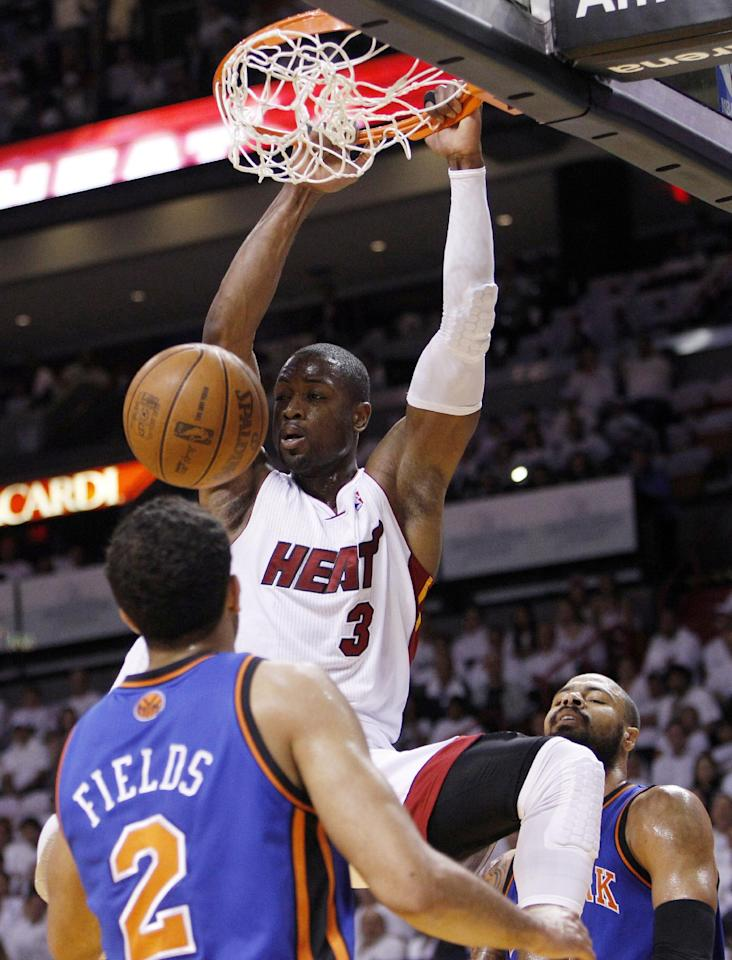 Miami Heat's Dwyane Wade (3) dunks in front of New York Knicks' Landry Fields (2) and Tyson Chandler, right, in the first half of an NBA basketball game in the first round of the Eastern Conference playoffs in Miami, Monday, April 30, 2012. (AP Photo/Lynne Sladky)