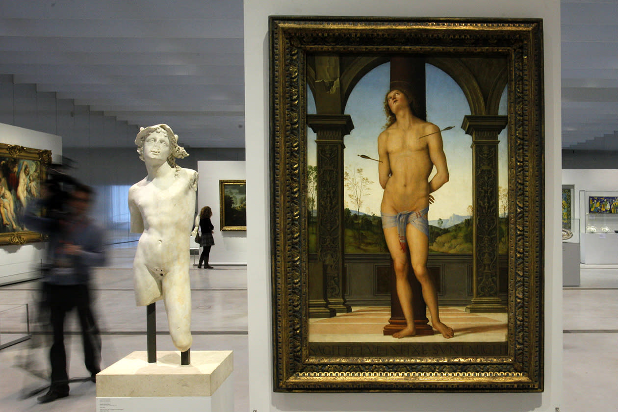 "A journalist walks past ""Saint Sebastien"" a painting by Pietro Di Cristforo Vannucci in the Louvre Museum in Lens."