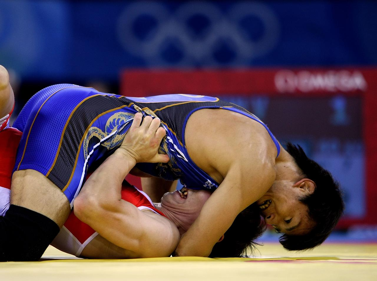 BEIJING - AUGUST 19:  Kenichi Yumoto (blue) of Japan competes against Vitaly Koryakin (red) of Tajikistan in the 60 kg freestyle wrestling event at the China Agriculture University Gymnasium on Day 11 of the Beijing 2008 Olympic Games on August 19, 2008 in Beijing, China.  (Photo by Jed Jacobsohn/Getty Images)