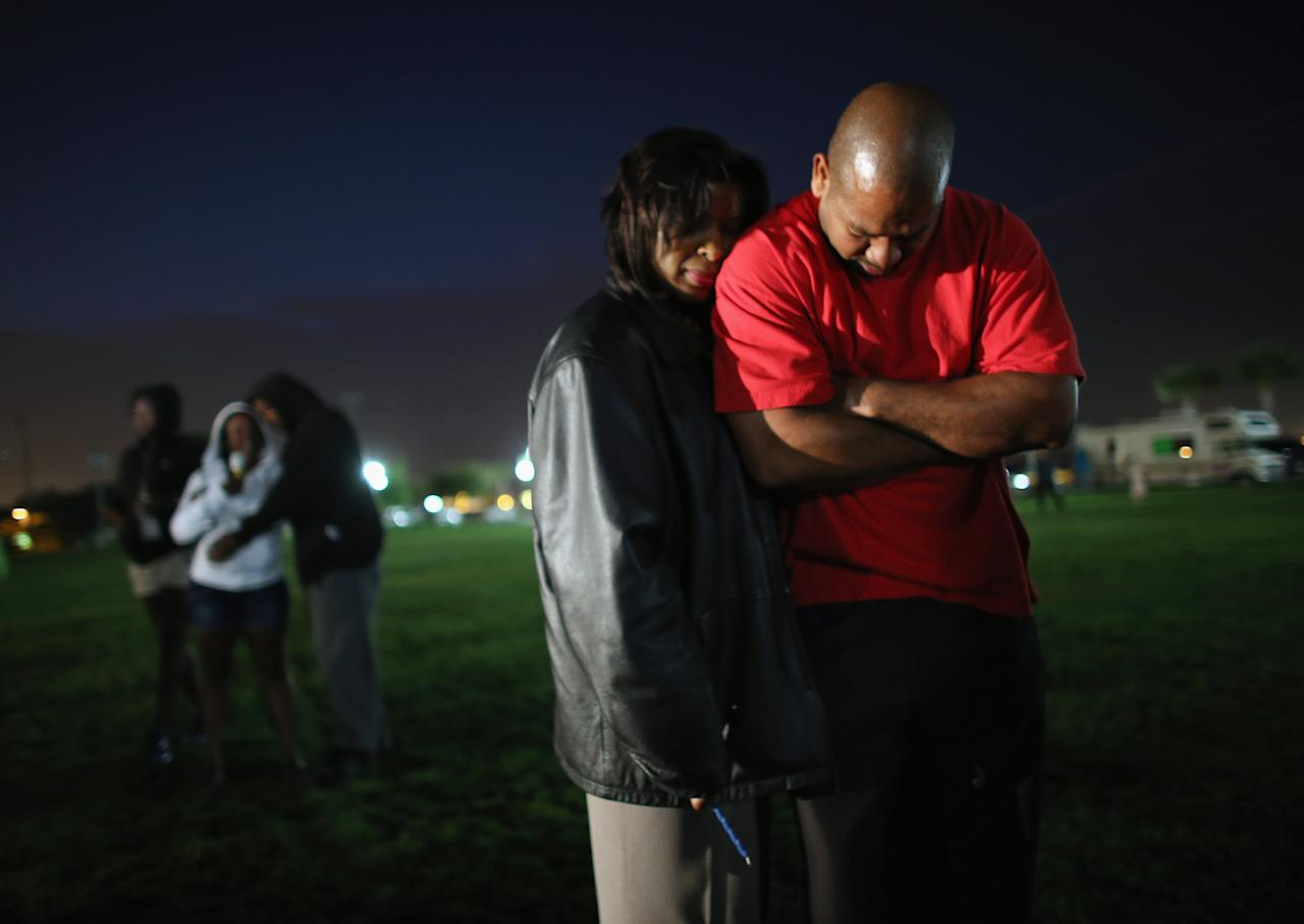 SANFORD, FL - FEBRUARY 26:  Claudia Robinson and Otis Robinson (L-R) stand together during a prayer before lighting candles during a vigil at Fort Mellon Park to mark the one year anniversary of when Trayvon Martin was killed on February 26, 2013 in Sanford, Florida. Martin was shot by George Zimmerman while Zimmerman was on neighborhood watch patrol in the gated community of The Retreat at Twin Lakes in Sanford, Florida.  (Photo by Joe Raedle/Getty Images)